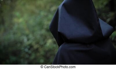 woman is wearing black raincoat with hood is walking fast in...