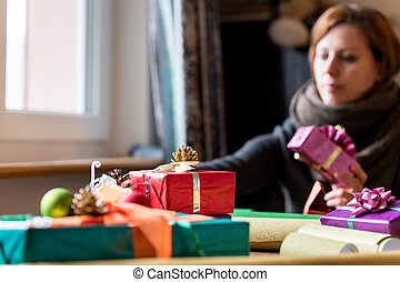 woman is wrapping a gift