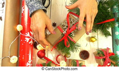 woman is wrapping Christmas presents on the table, concept...