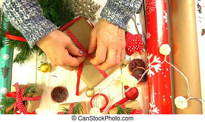 woman is wrapping Christmas presents on the table, concept of preparing for the New Year and Christmas holidays