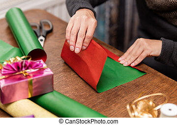 woman is wrapping colorful gifts