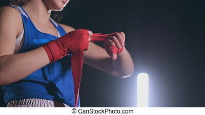 Woman is wrapping hands with yellow boxing wraps. Self Defense for Women. Isolated on black with red nails. Strong hand and fist, ready for fight and active exercise.