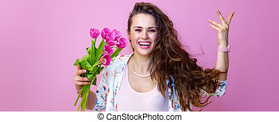 woman isolated on pink background with bouquet of flowers