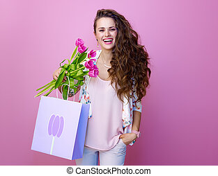 woman isolated on pink with bouquet of tulips and shopping bag