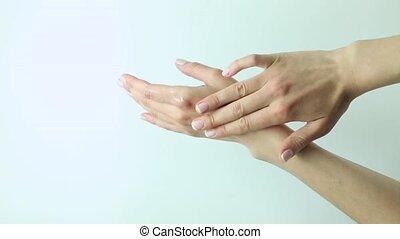 woman isolated on studio shot applying cream on her hands.