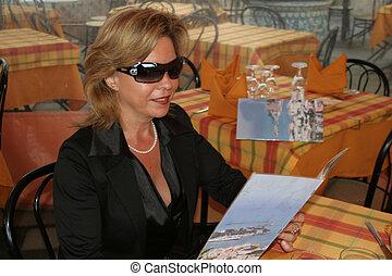 woman, italian restaurant - woman is studying the menucard...