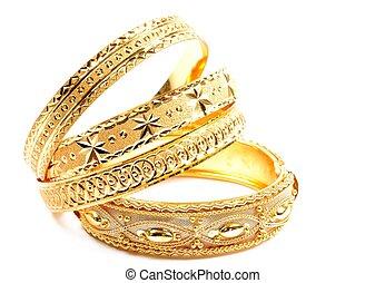 Woman jewelry - Three golden bracelets , on a white ...