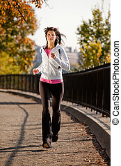 Woman Jogging -  A young woman jogging in the park on a path