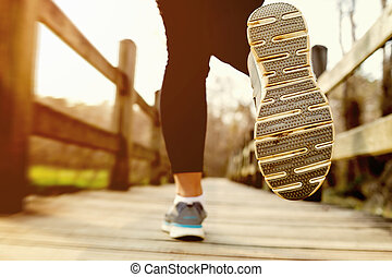Woman jogging across a country bridge at sunset