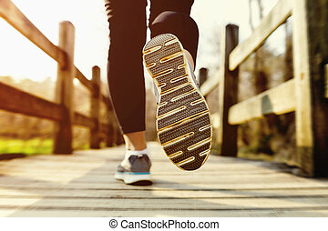 Woman jogging across an old country bridge at sunset