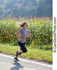 woman jogging along a country road