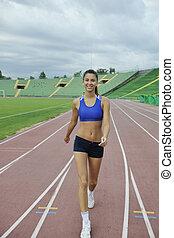 woman jogging at athletics stadium - beautiful young woman...