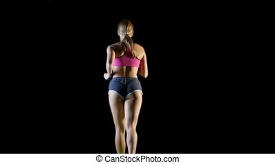 Woman jogging back view on a black background