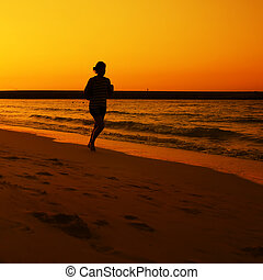 Woman jogging during Sunset over Jumeira beach in Dubai.