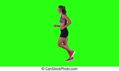 Woman jogging in a medium frontal shot. Green screen. Slow motion