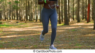 Woman jogging in the forest 4k - Woman jogging in the forest...