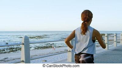 Woman jogging near beach 4k - Rear view of woman jogging...