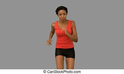 Woman jogging on grey screen in slow motion