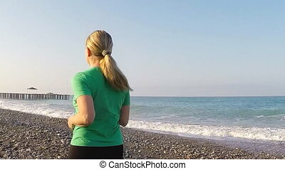 Woman jogging on the beach, slow motion