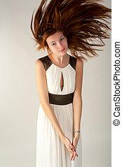 Woman joyful and happy in white dress. Flying hair
