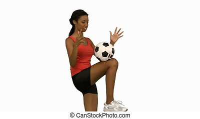 Woman juggling a football on white screen in slow motion