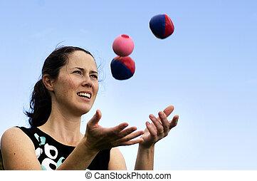 Woman Juggling Balls - Young woman juggler is juggling...