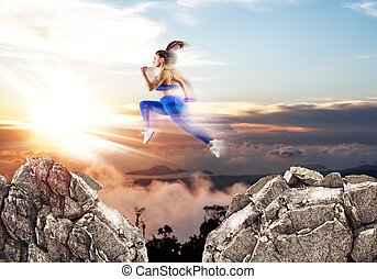 Woman jump through the gap between hills over sunset background.