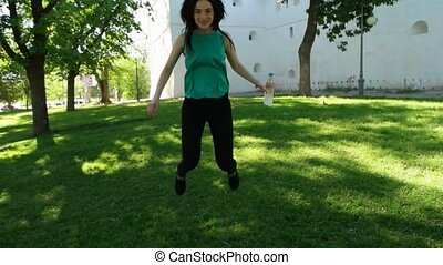 Woman jumping around feeling happy and free with water bottle in arms