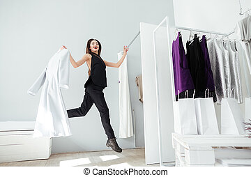 Woman jumping in clothing store