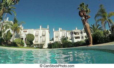 Woman jumping in pool - Side view of anonymous excited woman...