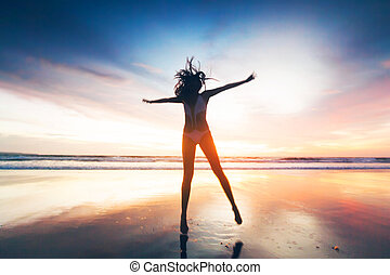 Woman jumping on beach at sunset