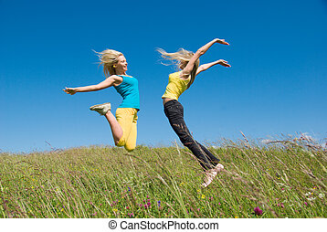 woman jumping on meadow and blue sky