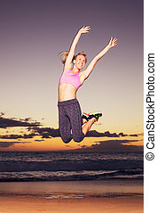 Woman jumping on the beach at sunset