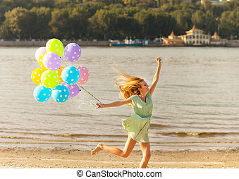 Woman jumping on the beach with colored polka dots balloons