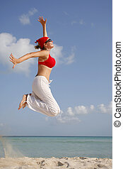 Woman in red clothes jumping on a beach