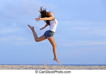 Woman jumping on the sand of the beach with the horizon in...