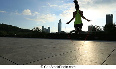 woman jumping rope at sunrise city