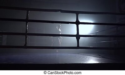 Woman jumping rope in a dark room . Silhouette. Slow motion...