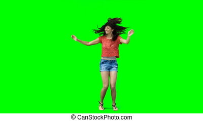 Woman jumping slightly and dancing against a green...