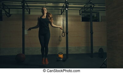 Woman jumping with a skipping rope in a gym