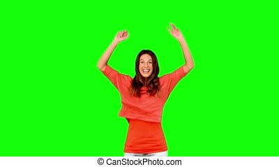 Woman jumping with arms raised on green screen in slow motion