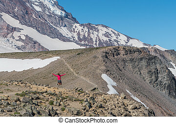 Woman Jumps along Trail to Burroughs Mountain with view of Mount Rainier