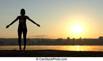 Woman jumps, clasps her hands up, at a nice sunset in slo-