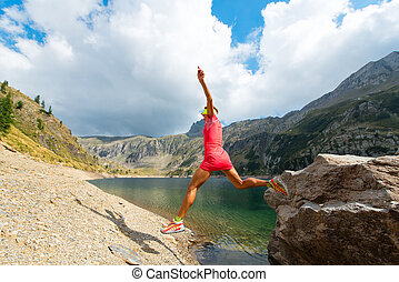 Woman jumps from a rock near a mountain lake