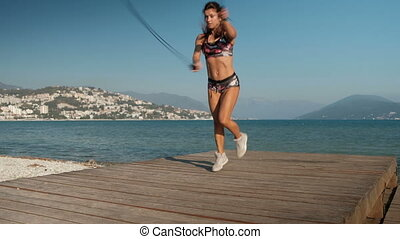 Woman jumps with two skipping ropes and does exercises on beach.