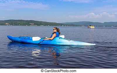 woman kayaking on a calm lake