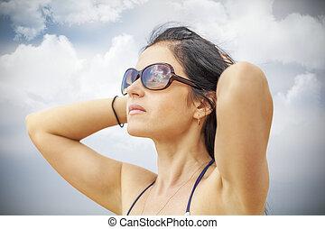Woman keep the hair on the cloudy