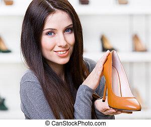 Woman keeping brown heeled shoe