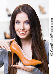 Woman keeping brown stylish shoe