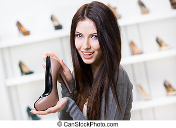 Woman keeping coffee-colored shoe